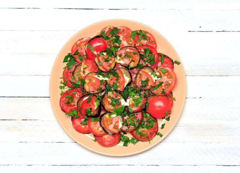 Gebraden aubergine met tomaten, knoflook en mayonaise op een witte houten achtergrond, hoogste mening royalty-vrije stock foto's