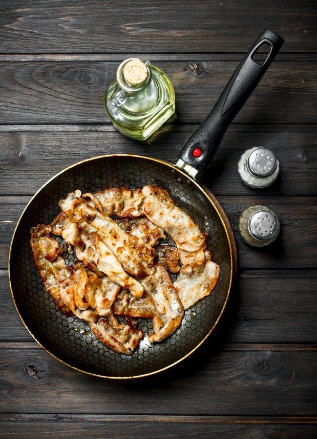 Gebraden bacon in een pan met kruiden stock fotografie