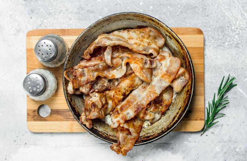 Gebraden bacon in een pan met kruiden royalty-vrije stock fotografie