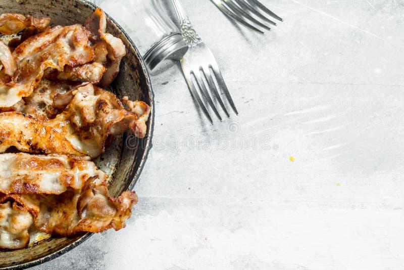 Gebraden bacon in een pan met kruiden stock foto's