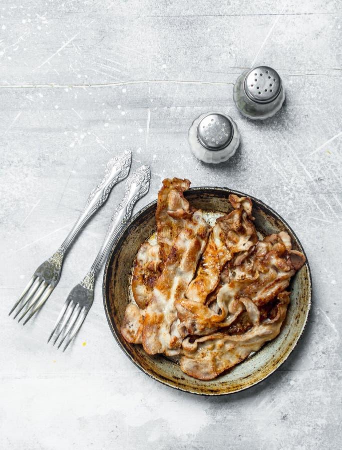 Gebraden bacon in een pan met kruiden stock foto