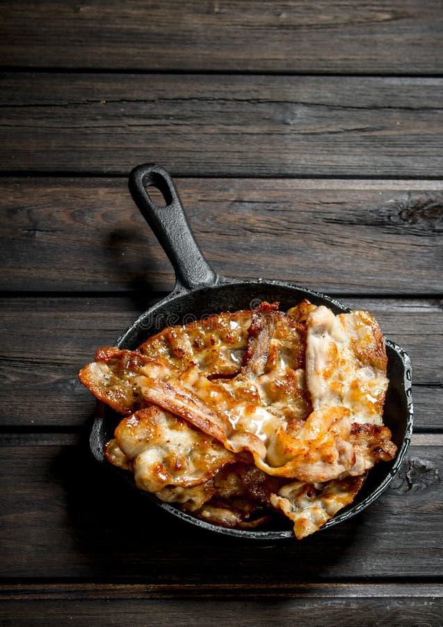 Gebraden bacon in een pan stock foto