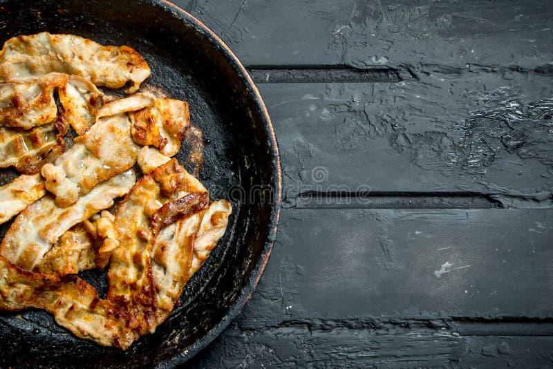 Gebraden bacon in een pan stock afbeelding