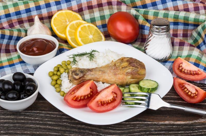 Gebraden benen, rijst, groente, citroenen, zwarte olijven en ketchup stock foto