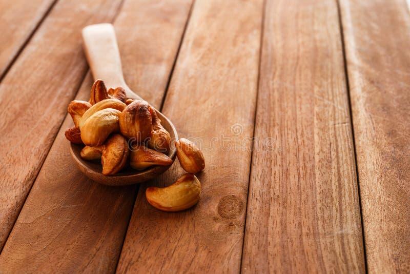Gebraden cashewnoten in een houten lepel stock foto's