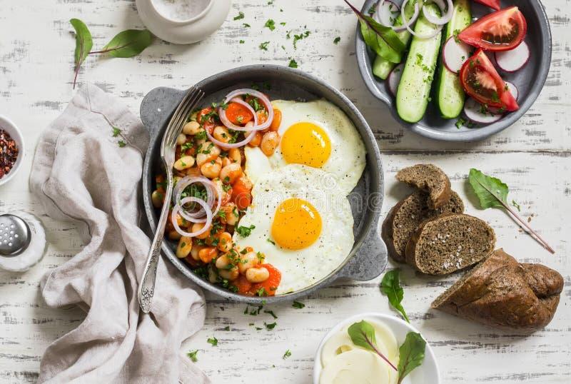 Gebraden ei, bonen in tomatensaus met uien en wortelen, verse komkommers en tomaten, eigengemaakt roggebrood - heerlijk ontbijt royalty-vrije stock foto
