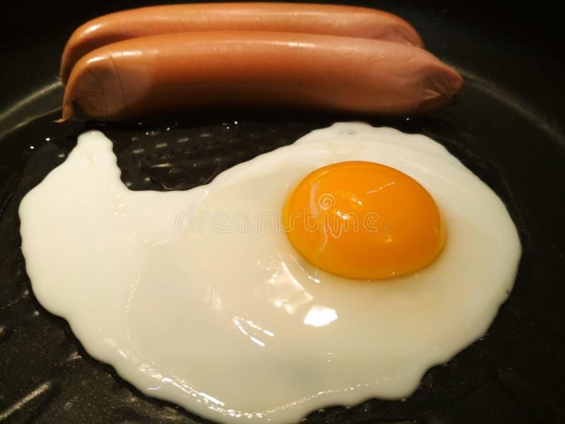Gebraden ei in een pan met worst Close-up van gebraden eieren stock foto