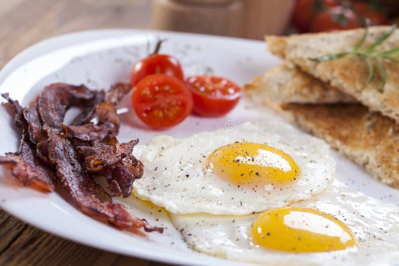 Gebraden ei en bacon op een plaat met kruiden en groenten royalty-vrije stock foto