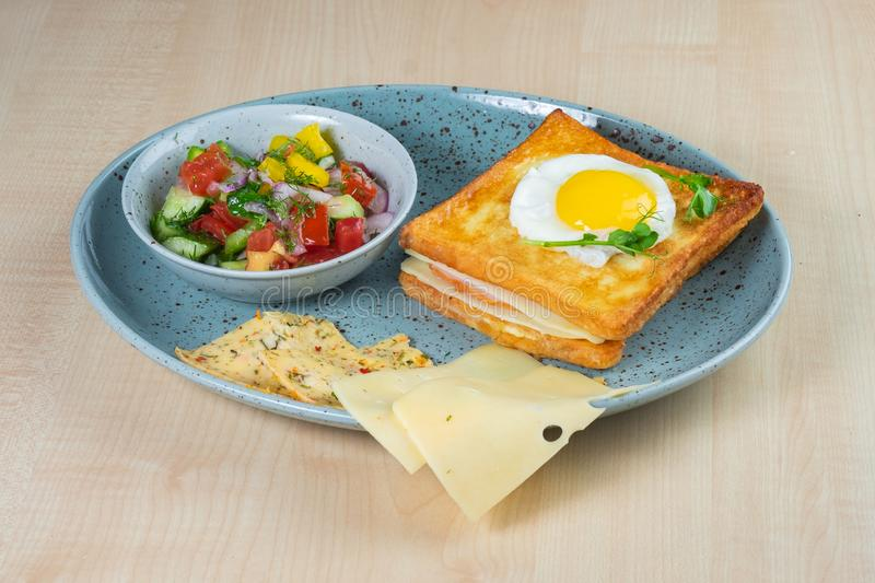 Gebraden ei en hamsandwich, tomaat, komkommer en pepersalade en kaas op een plaat stock fotografie