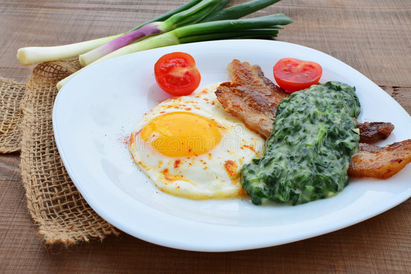 Gebraden ei met afgeroomd spinazie en bacon stock afbeelding