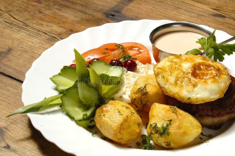 Gebraden ei met lapje vlees en aardappelen in de schil stock foto