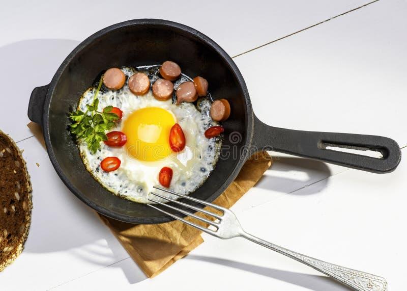 Gebraden ei met stukken van worst in een ronde zwarte gietijzerfryi royalty-vrije stock afbeelding