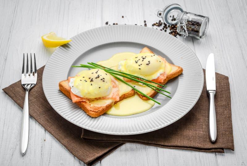 Gebraden ei op brood voor ontbijt op plaat en rustieke lijst, met zalm stock foto's