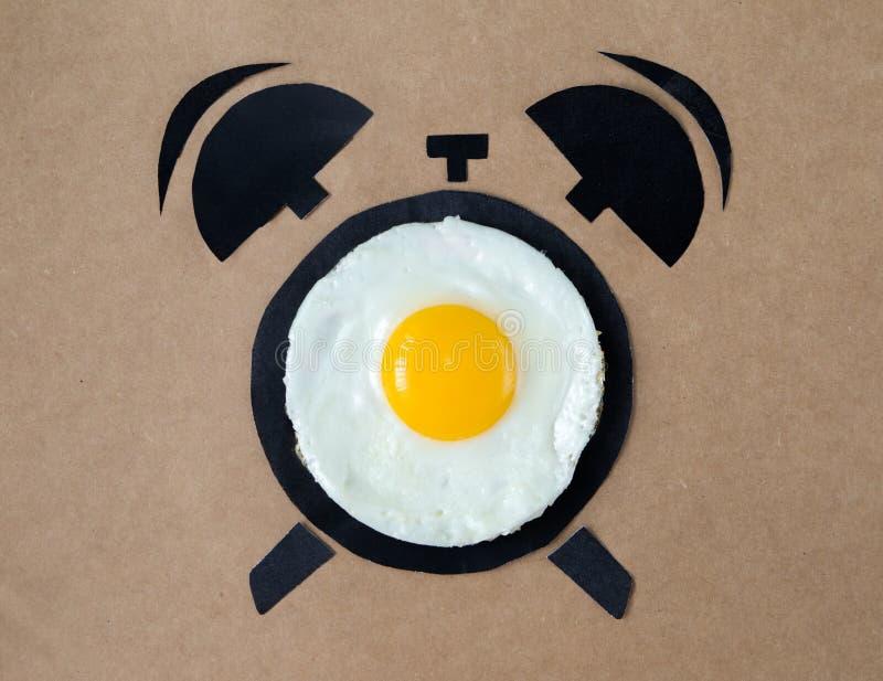 Gebraden ei in vorm van wekker, het concept van de ontbijttijd stock afbeelding