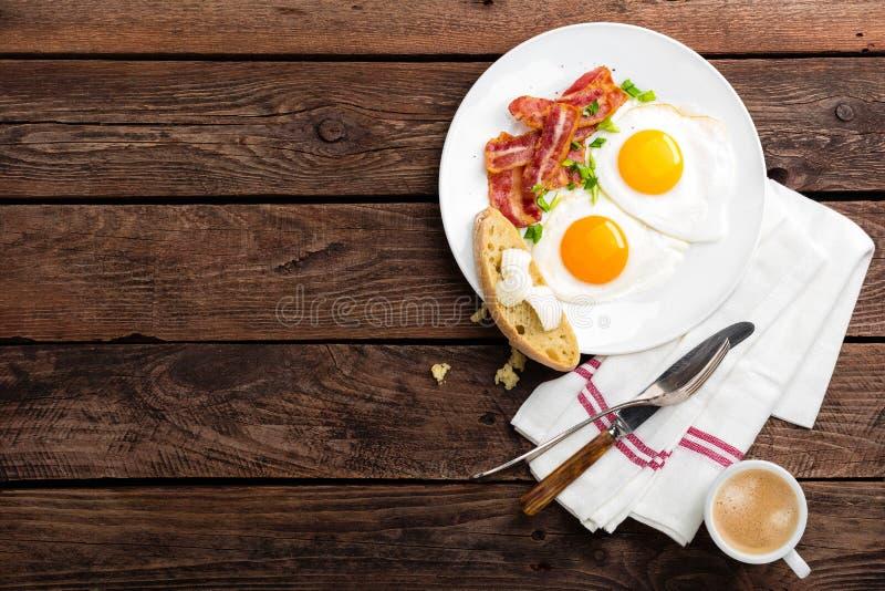 Gebraden eieren, bacon en Italiaans ciabattabrood op witte plaat Kop van koffie Ontbijt hoogste mening Houten achtergrond stock foto's