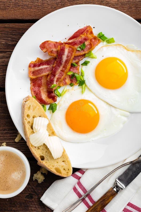 Gebraden eieren, bacon en Italiaans ciabattabrood op witte plaat Kop van koffie Ontbijt hoogste mening Houten achtergrond stock afbeeldingen