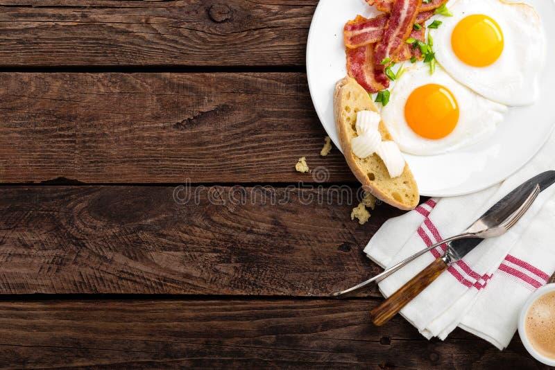 Gebraden eieren, bacon en Italiaans ciabattabrood op witte plaat Kop van koffie Ontbijt hoogste mening Houten achtergrond royalty-vrije stock foto