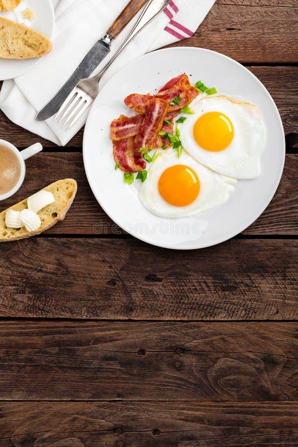 Gebraden eieren, bacon en Italiaans ciabattabrood op witte plaat Kop van koffie Ontbijt hoogste mening Houten achtergrond royalty-vrije stock afbeeldingen