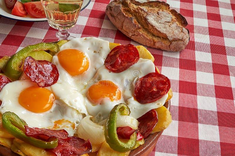 Gebraden eieren, chorizo, gebraden aardappels, groene paprika en ui stock afbeelding