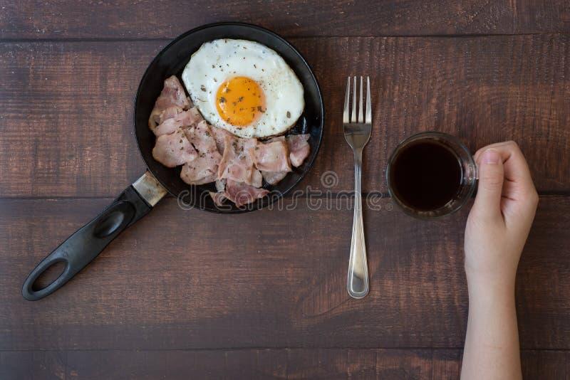 Gebraden eieren in een pan en een koffie stock afbeeldingen