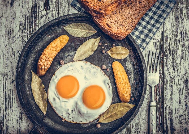Gebraden eieren in een pan Roggetoost en ingelegde komkommer naast gebraden eieren stock fotografie