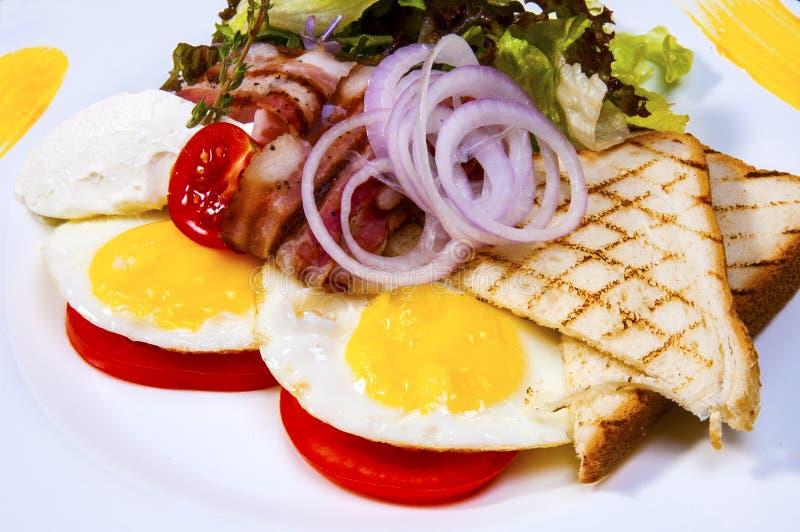 Gebraden eieren met bacon stock afbeelding
