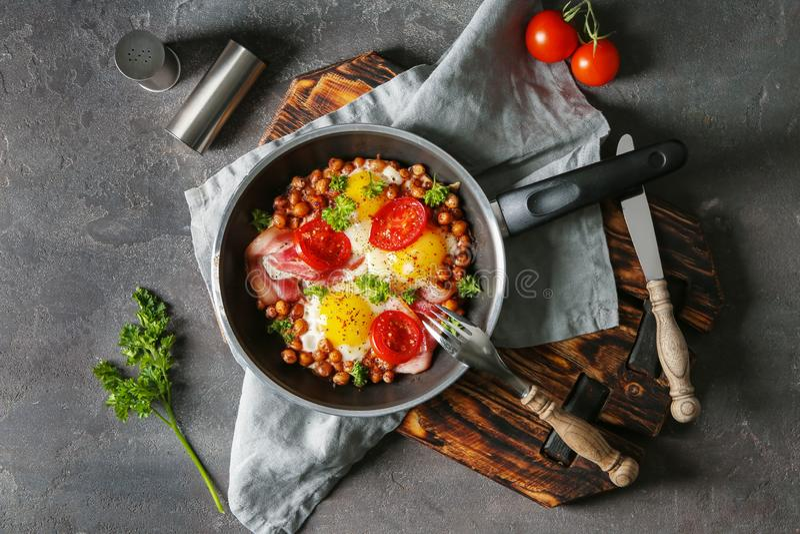 Gebraden eieren met bacon en kekers in pan op lijst royalty-vrije stock afbeeldingen