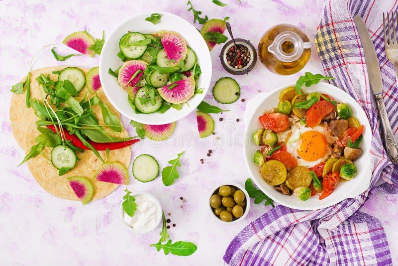 Gebraden eieren met groenten - shakshuka en verse saladekomkommer, watermeloenradijs en arugula royalty-vrije stock fotografie