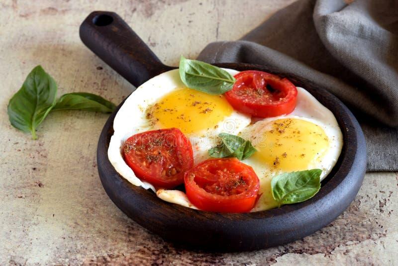 Gebraden eieren met kruiden, Basilicum en plakken van rijpe tomaat in een pan, die gefotografeerd close-up op een grijze achtergr royalty-vrije stock afbeelding