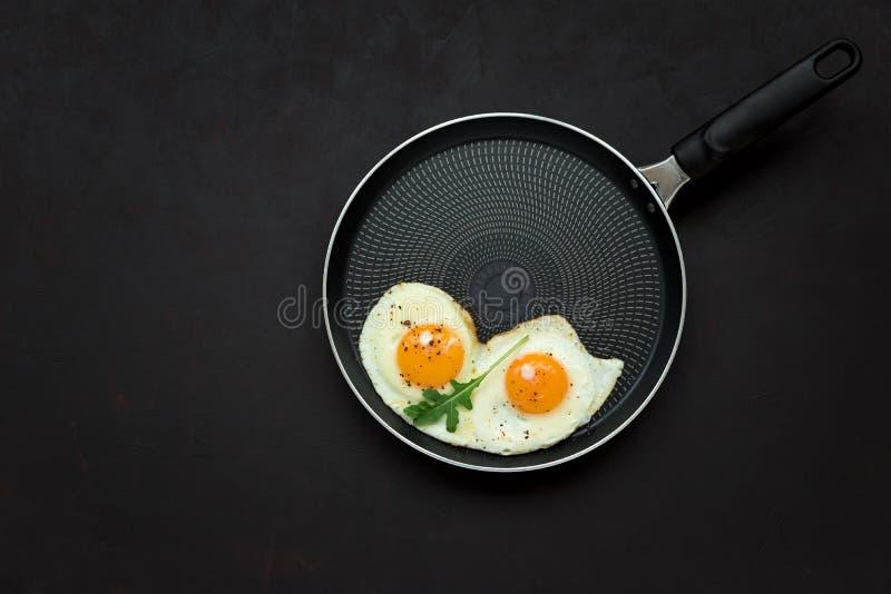 Gebraden eieren in pan met arugulabladeren, zout en peper voor ontbijt op zwarte houten achtergrond Hoogste mening Vlak leg exemp stock afbeelding