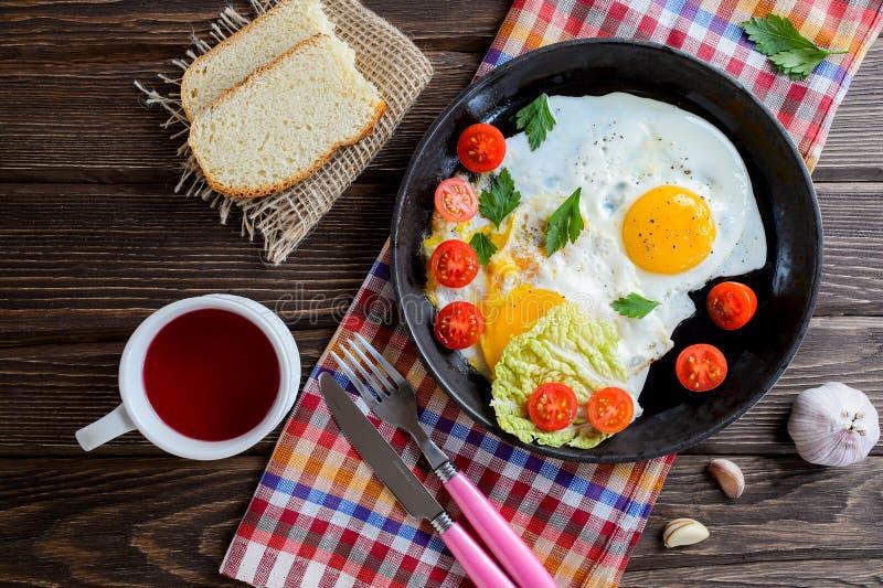 Gebraden eieren in pan met tomaat, brood, peper en peterselie stock foto