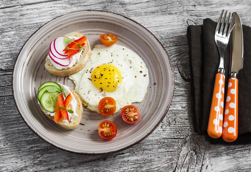 Gebraden eieren, tomaten en sandwiches met komkommer, radijs en zachte kaas Op een lichte houten lijst Rustieke stijl stock fotografie