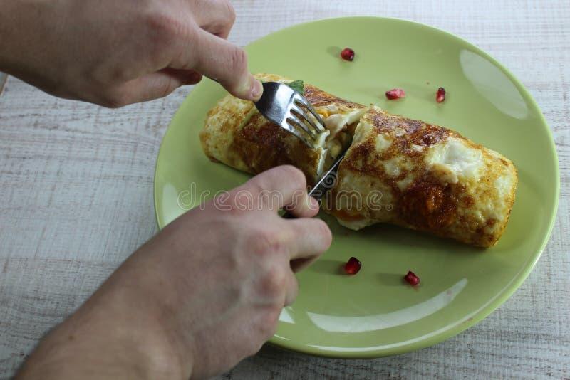 Gebraden eierenomelet op een groen rond plaatknipsel met dicht omhoog mes en vork in handen stock foto