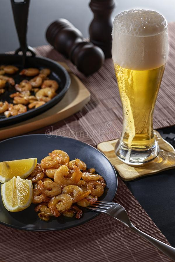 Gebraden garnalen en citroen in een zwarte plaat met glas bier royalty-vrije stock afbeelding