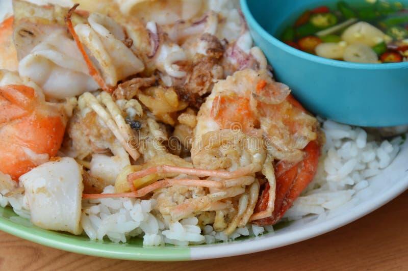 Gebraden garnalen en pijlinktvis met knoflook op rijst stock afbeeldingen
