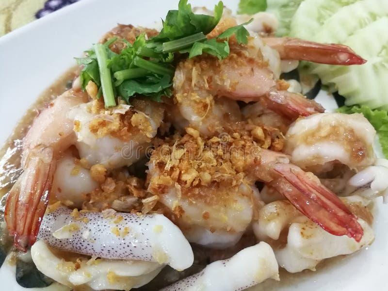 Gebraden garnalen en pijlinktvis met knoflookpeper op het Voedsel van plaat/Thai stock foto's