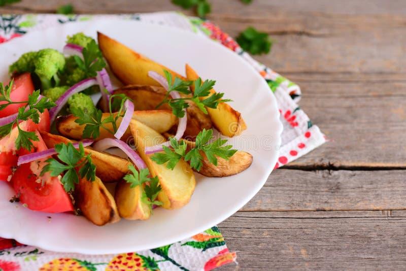 Gebraden gerechten, gekookte broccoli, verse tomaat met kruiden, rode ui, peterseliebladeren op een witte plaat en op een oude ho royalty-vrije stock foto's