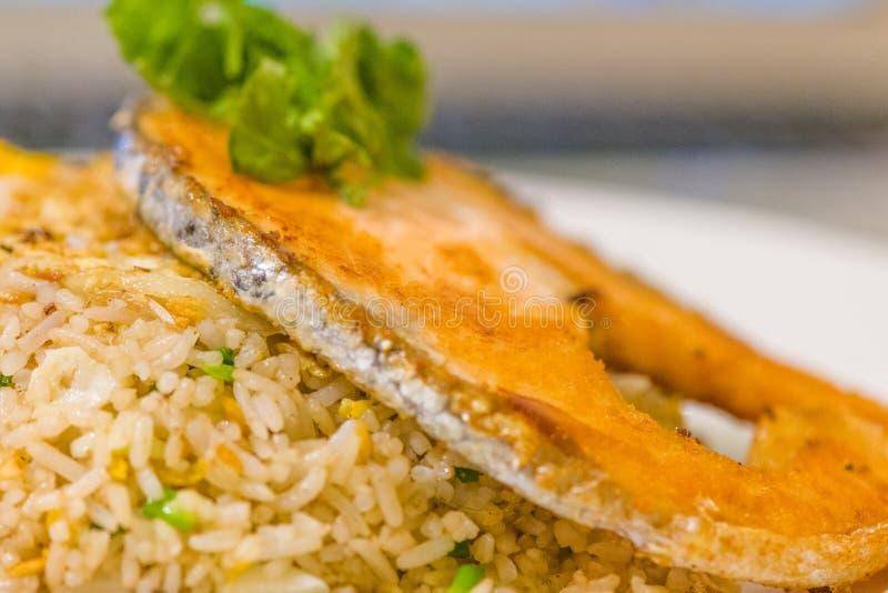 gebraden gesneden zalm met gebraden rijst het gebruiksvork en lepel van mensenhanden voor fusievoedsel gesneden zalm met binnen r royalty-vrije stock afbeeldingen