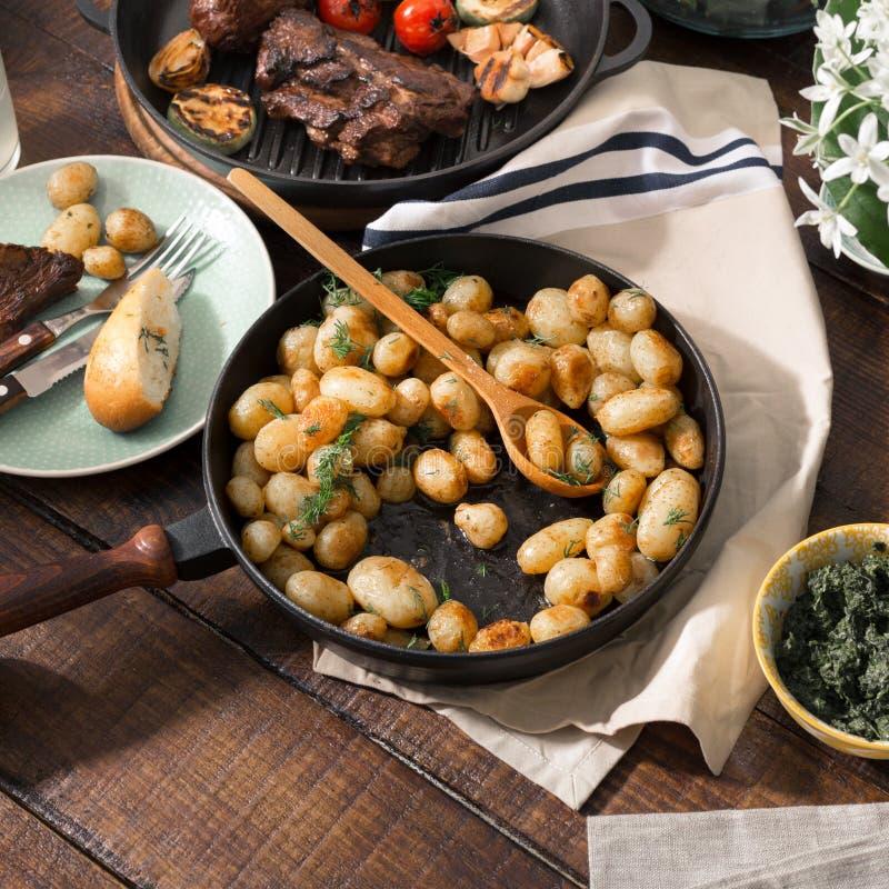 Gebraden jonge aardappels in pan met geroosterd vlees stock foto