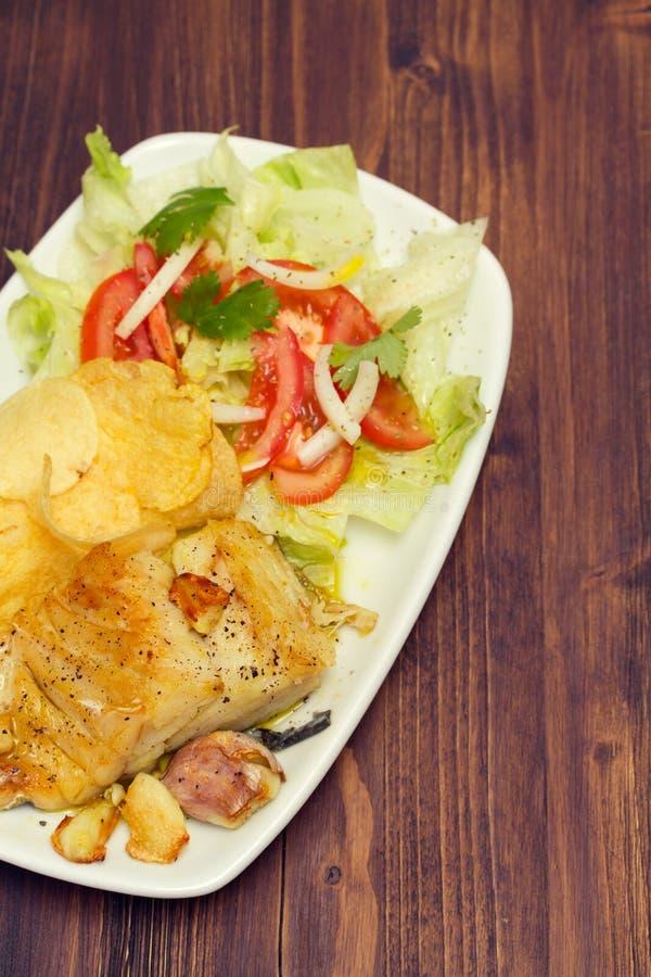 Gebraden kabeljauw met aardappel en salade op schotel royalty-vrije stock foto
