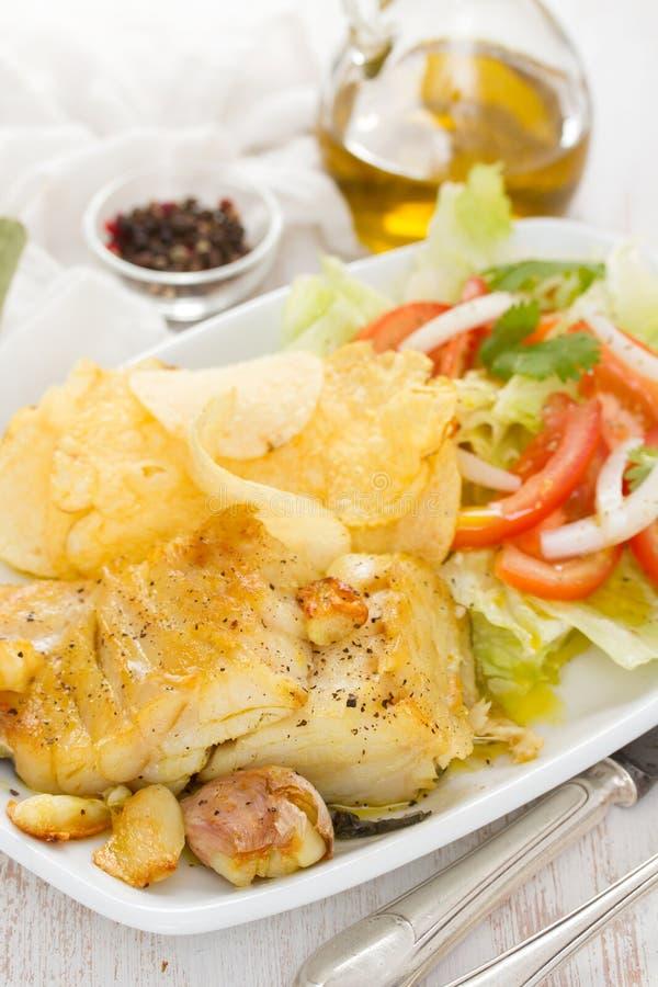 Gebraden kabeljauw met aardappel en salade op schotel royalty-vrije stock fotografie