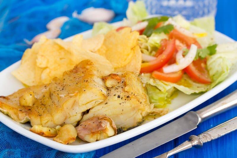 Gebraden kabeljauw met aardappel en salade op schotel royalty-vrije stock afbeelding