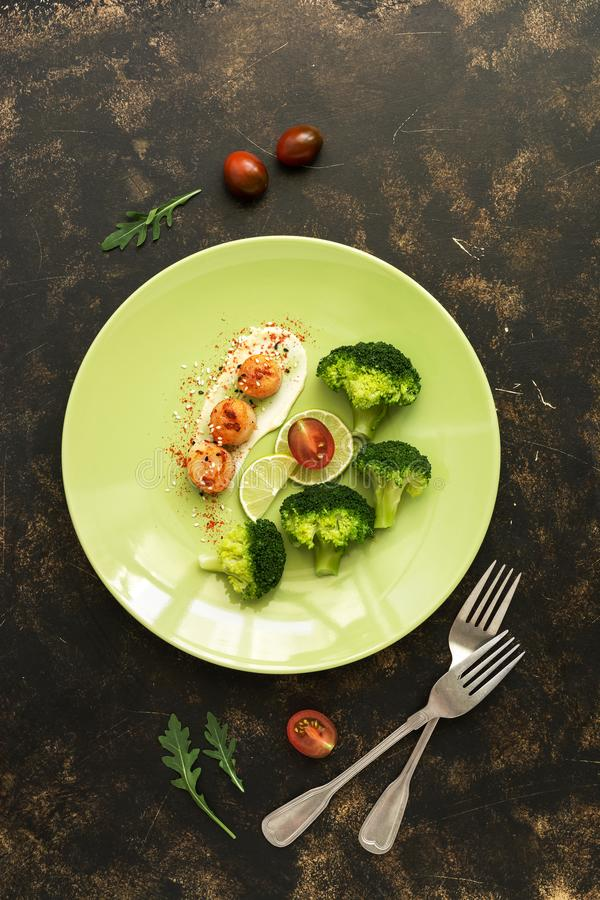 Gebraden kammosselen met broccoli, kalk, saus in een plaat op een donkere rustieke achtergrond Overzees voedseldelicatesse De hoo royalty-vrije stock afbeelding