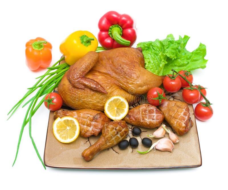Gebraden kip en verse groenten op scherpe raad op witte bac stock afbeelding