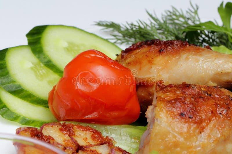 Gebraden kippenbenen met groenten in een plaat stock foto's