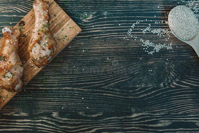 Gebraden kippenbenen met kruiden op een houten dienblad Plaats voor tekst Mening van hierboven stock afbeeldingen