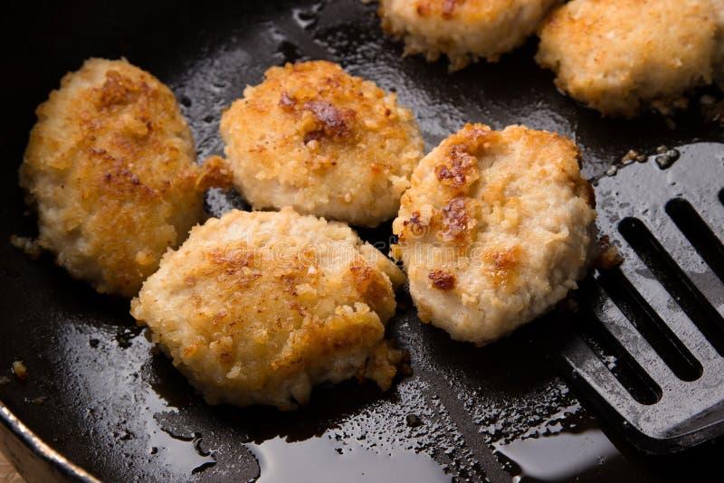Gebraden kippenkoteletten met een knapperige korst in olie, in een pan, close-up Heerlijke ongezonde kost Speciaal voor een snack stock afbeelding