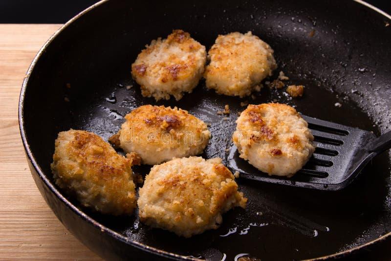 Gebraden kippenkoteletten met een knapperige korst in olie, in een pan Heerlijke ongezonde kost Speciaal voor een snack terwijl h stock fotografie