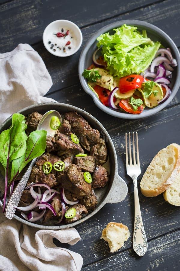 Gebraden kippenlever en geroosterde groenten - courgette, Spaanse pepers, uien en verse groene salade stock foto