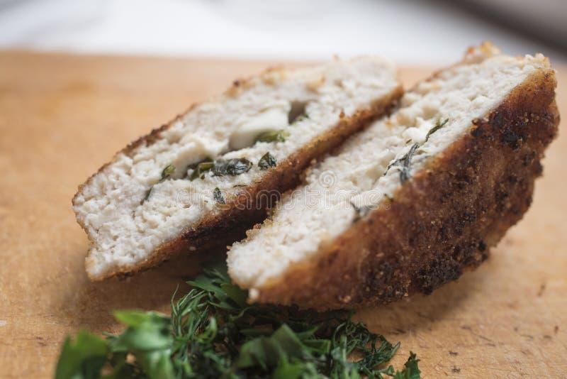 Gebraden koteletten met kaas en greens op een houten achtergrond stock afbeeldingen